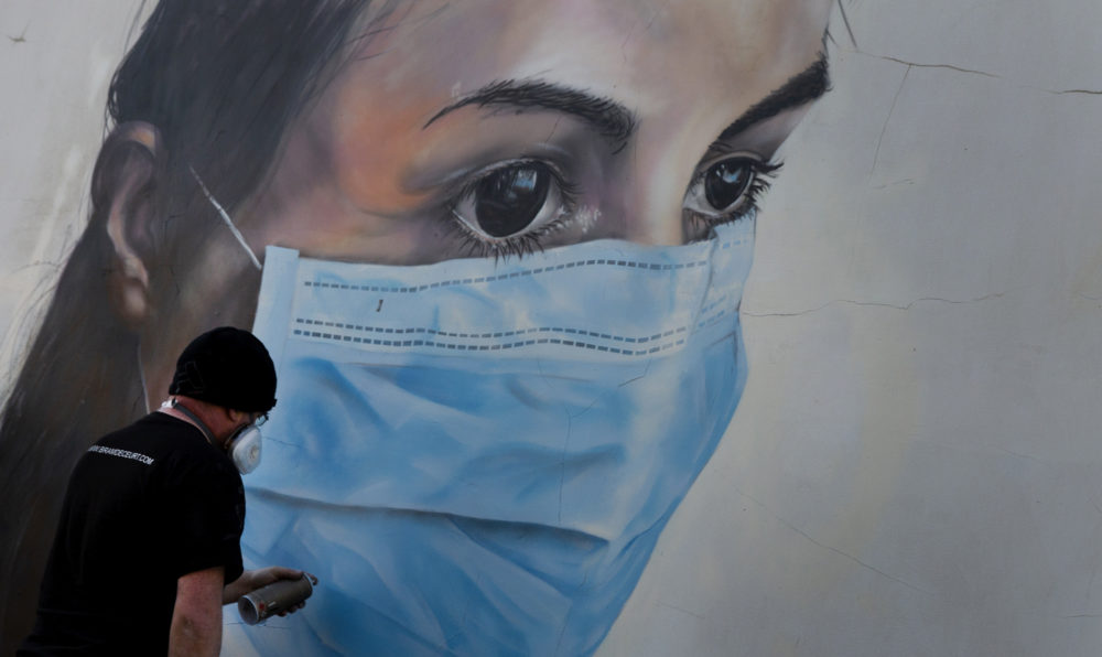Graffiti artist Bram De Ceurt works on a painting of a nurse with a mask to protect against coronavirus in Antwerp, Belgium, Thursday, March 26, 2020. (Virginia Mayo/AP)