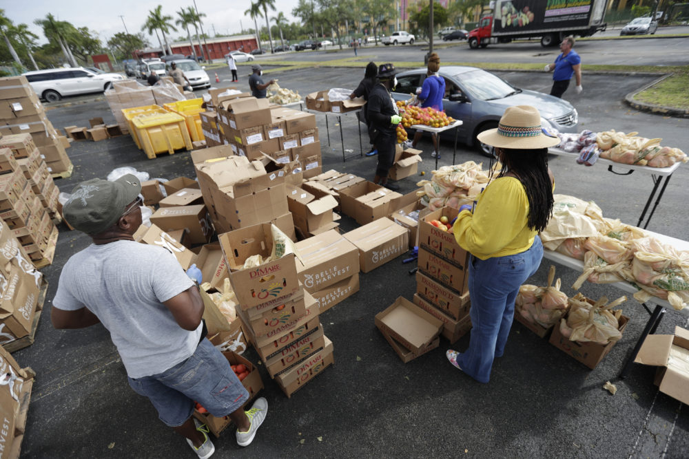 Workers hand out bags of food during a food distribution event, Wednesday, April 1, 2020, in the Liberty City neighborhood of Miami. (Wilfredo Lee/AP Photo)