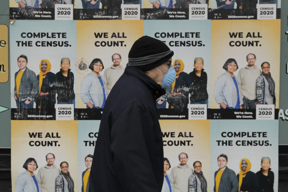 A man wearing a mask walks past posters encouraging participation in the 2020 Census, Wednesday, April 1, 2020, in Seattle's Capitol Hill neighborhood. (Ted S. Warren/AP)
