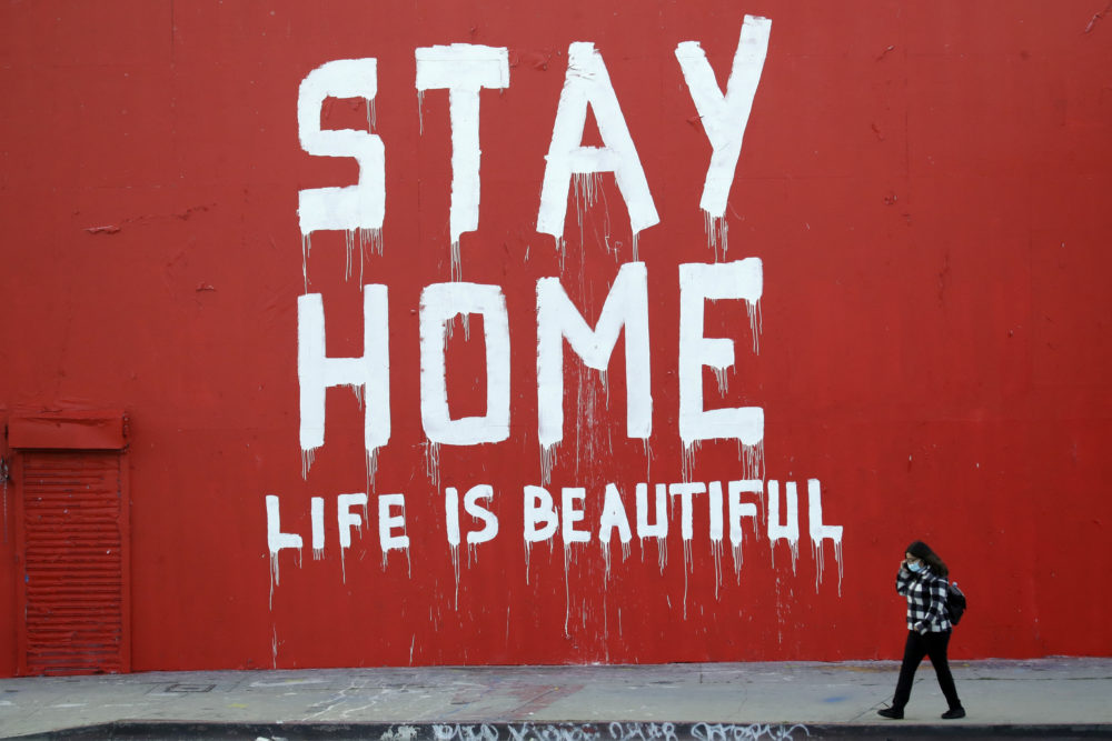 "A pedestrian walks past a mural which reads ""Stay at Home, Life is Beautiful"" Thursday, April 2, 2020, in Los Angeles. (Marcio Jose Sanchez/AP Photo)"