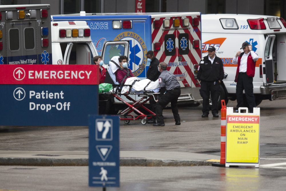 An ambulance crew transports a patient at the Massachusetts General Hospital emergency entrance in April (Michael Dwyer/AP)