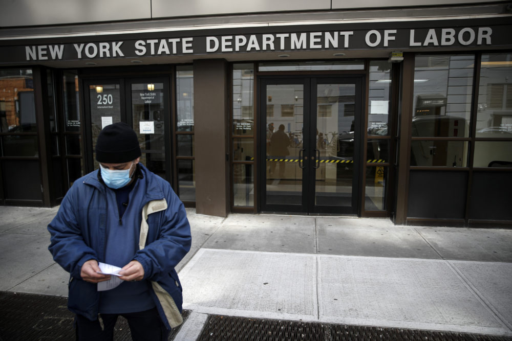 Visitors to the Department of Labor are turned away at the door by personnel due to closures over coronavirus concerns in New York. Americans are seeking unemployment benefits at unprecedented levels due to the coronavirus, but many are finding more frustration than relief. (John Minchillo/AP)