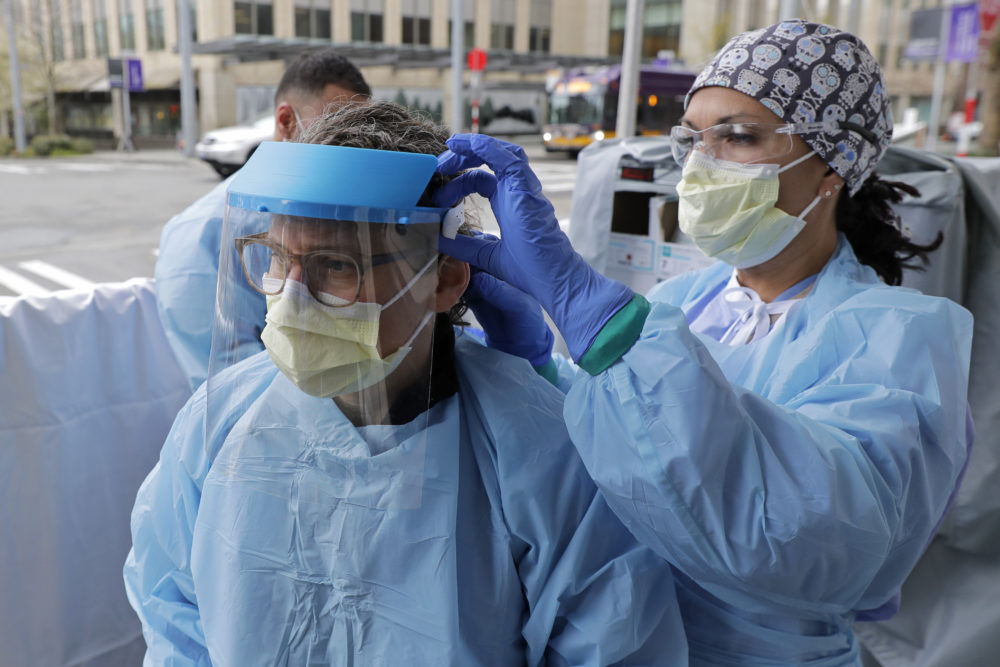In this April 2, 2020 photo, Tilliesa Banks, right, an emergency services nurse at Harborview Medical Center in Seattle, helps a colleague put on a medical face shield. (Ted S. Warren/AP)