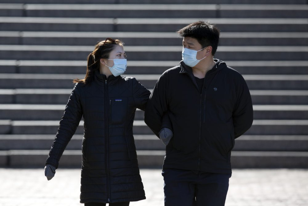 A couple wears protective masks while walking at Faneuil Hall, Saturday, April 4, 2020, in Boston. (AP Photo/Michael Dwyer)