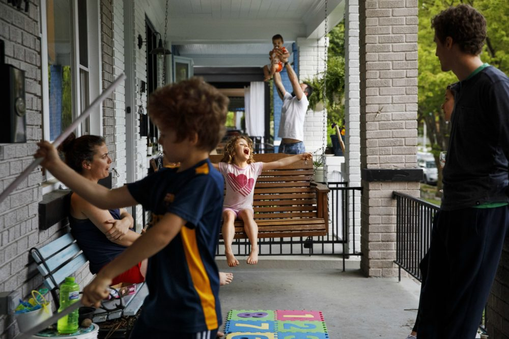 Carys Williams, 7, center, plays on the family porch swing as her brother Owain, 8, left, plays with metal rods, and Gavin Tropeano, 9 months, is swung up in the air by his father Andrew Tropeano, as neighbors spend extra time on their porches since schools and offices closed due to the coronavirus, Sunday April 5, 2020, in Washington. (Jacquelyn Martin/AP)