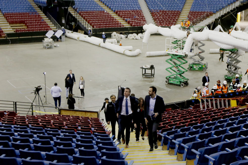 Gov. Gavin Newsom, front left, accompanied by Jason Kenney, front right, deputy director of the Real Estate Services Division of the Department of General Services, tours Sleep Train Arena, the former home of the NBA's Sacramento Kings basketball team in Sacramento, Calif., Monday, April 6, 2020. The arena is being transformed into a 400-bed emergency field hospital to help deal with the coronavirus outbreak. (Rich Pedroncelli/AP)