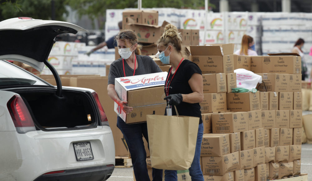Workers and volunteers help load cars at a San Antonio Food Bank drive-through distribution.  (Eric Gay/AP)