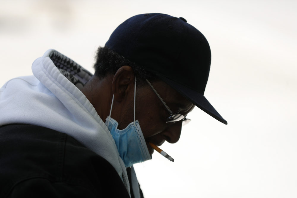 A man smokes a cigarette while wearing a protective mask while waiting for a bus in Detroit. (Paul Sancya/AP)