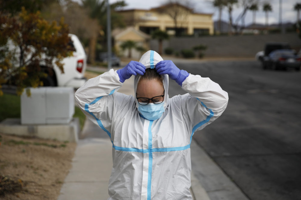 Paramedic Chelsea Monge of Ready Responders removes personal protective equipment after making a house call for a possible coronavirus patient Friday, April 10, 2020, in Henderson, Nev. (John Locher/AP)