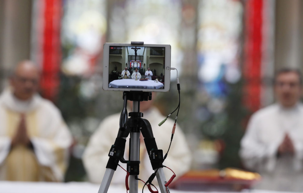 A recording device captures the delivery of Easter Mass in Queen of Peace Catholic Church in Aurora, Colo. (AP Photo/David Zalubowski)