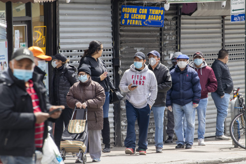 People wear face masks to protect against the coronavirus as they stand on line to grocery shop, Tuesday, April 14, 2020, in Corona neighborhood of the Queens borough of New York. (Mary Altaffer/AP)