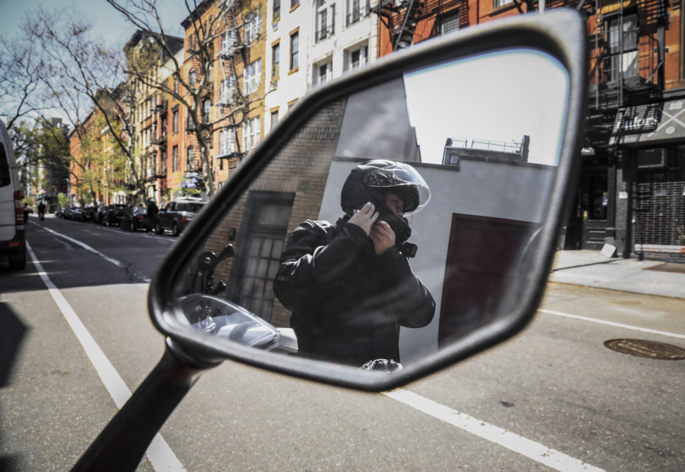 Eddie Song, a Korean American entrepreneur, prepares to ride his motorcycle wearing a jacket over extra body padding while equipped with video cameras, Sunday April 19, 2020, in East Village neighborhood of New York. After being blamed for causing the coronavirus outbreak in a recent assault, Song routinely wears the extra gear for extra safety. (AP Photo/Bebeto Matthews)