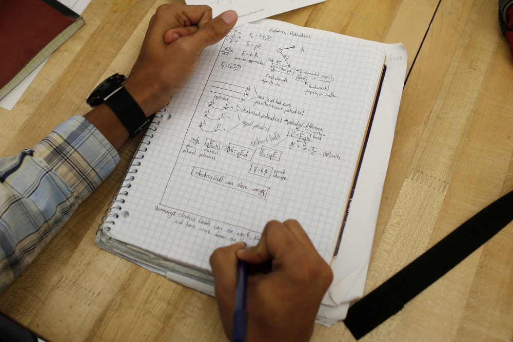 A student writes notes in the Advanced Placement (AP) Physics class at Woodrow Wilson High School in Washington, (Charles Dharapak/AP)