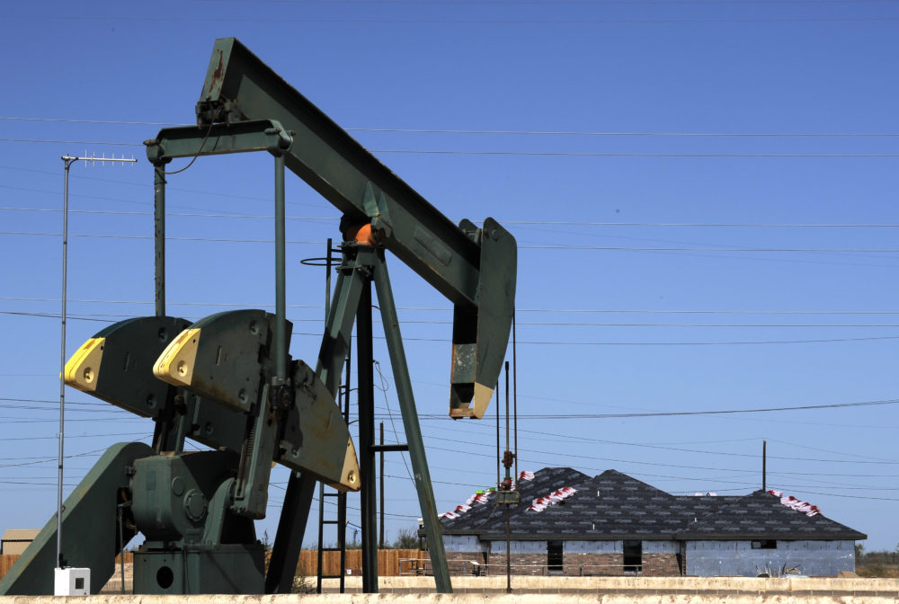 A pump jack works beside the site of new home construction in Midland, Texas. (Pat Sullivan/AP)