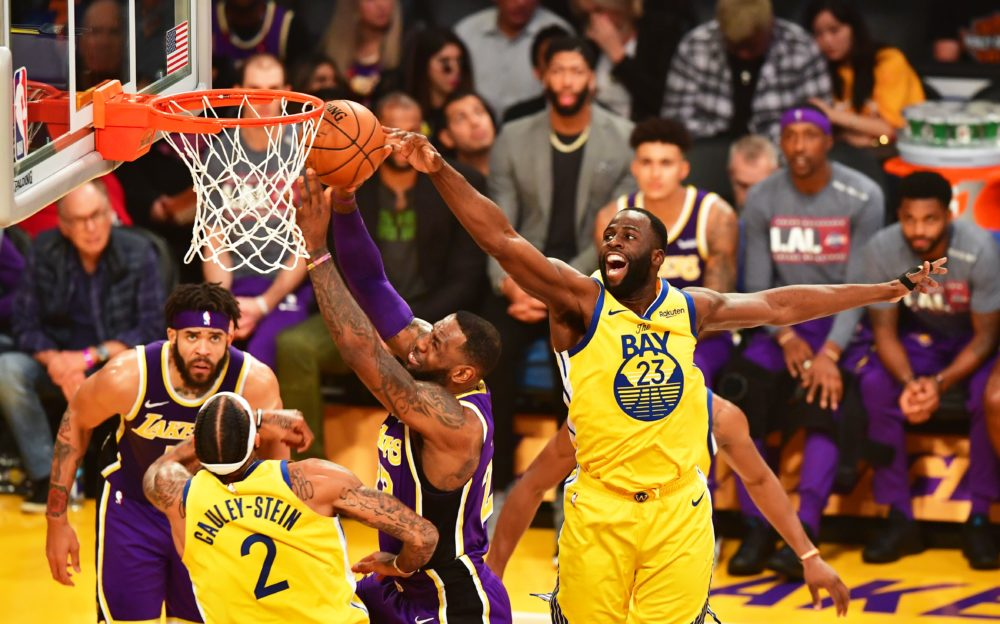 LeBron James of the Los Angeles Lakers (C) goes to the hoop under pressure from Draymond Green (R) of the Golden State Warriors during their the regular season game at the Staples Center in Los Angeles on November 13, 2019. (FREDERIC J. BROWN/AFP via Getty Images)