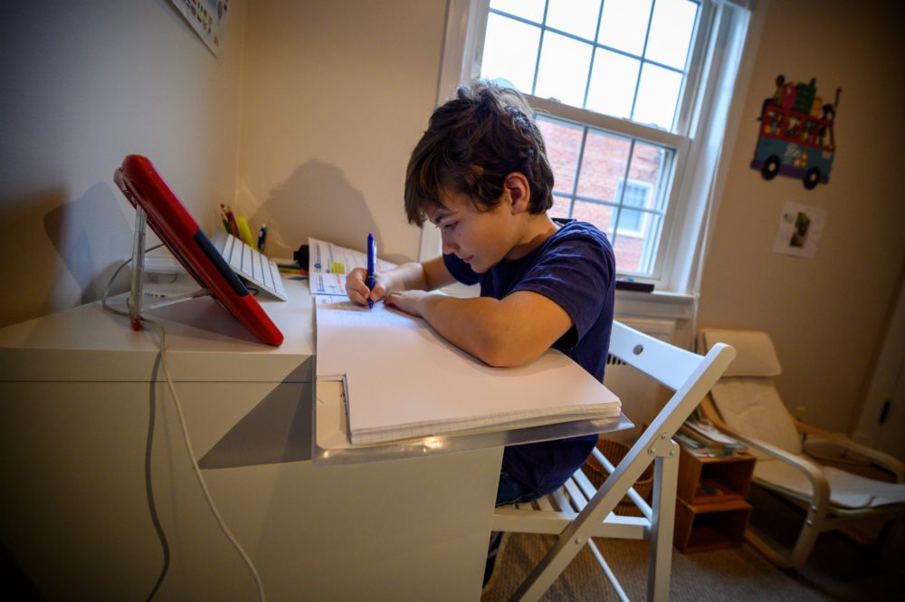Colin, 10, whose school was closed following the coronavirus outbreak, does school exercises at home in Washington on March 20, 2020. (ERIC BARADAT/AFP via Getty Images)