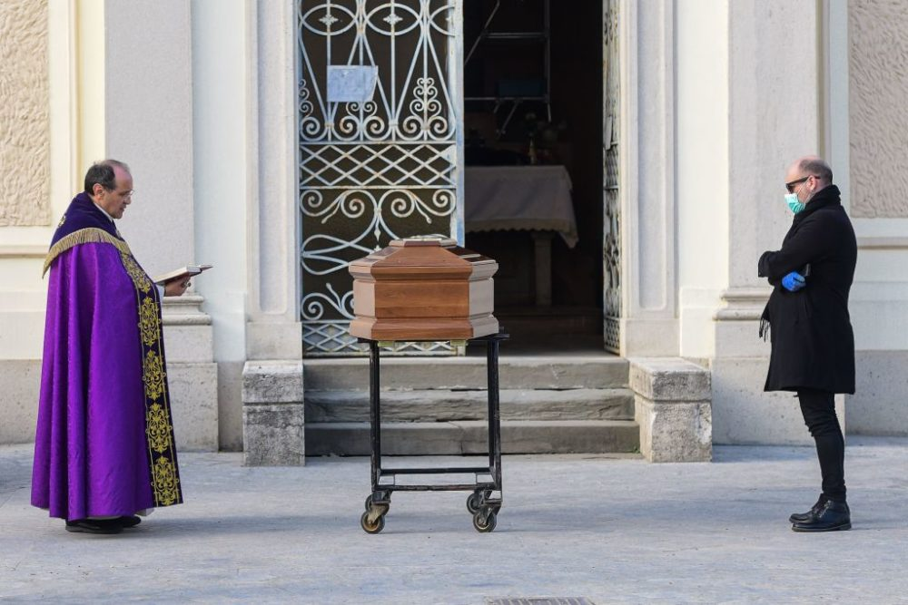 A man wearing a face mask stands by the coffin of his mother as a priest reads prayers. (Piero Cruciatti/AFP/Getty Images)