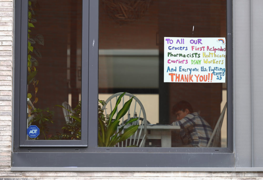A child sits at a table in an apartment with a window sign thanking workers on March 25, 2020 in New York (Angela Weiss/AFP/Getty Images)