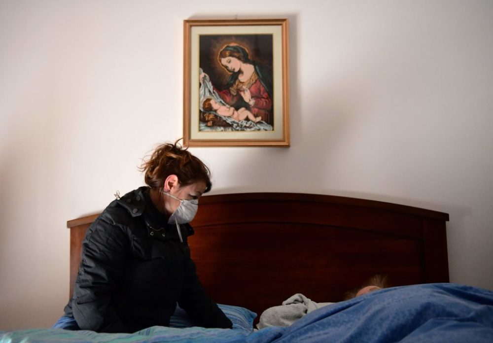 A woman talks to her 80-year-old mother, who is in bed with potential symptoms of COVID-19.(Piero Cruciatti/AFP/Getty Images)