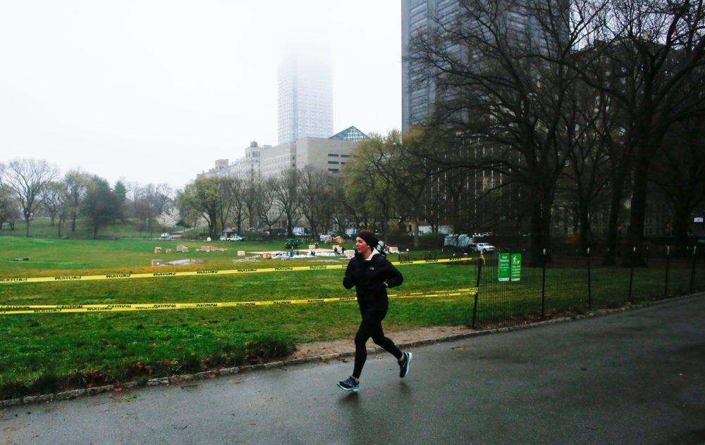 A woman jogs by Central Park as workers set up a field hospital in front of Mount Sinai West Hospital on March 29, 2020 in New York City. (KENA BETANCUR/AFP via Getty Images)