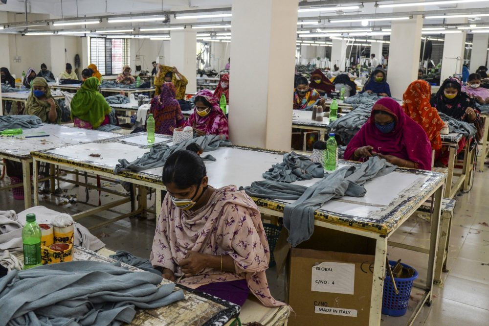 Garment workers wearing face masks work in a factory during a government-imposed lockdown as a preventative measure against the COVID-19 coronavirus on the outskirts of Dhaka on April 7, 2020. (Munir Uz Zaman/AFP/Getty Images)