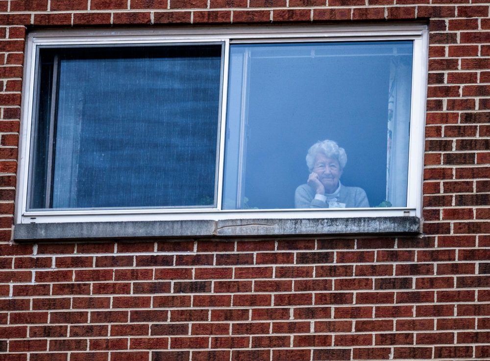 """A resident of the Goodwin House senior living community, looks on as she listens to the DC area motown band """"The Tribe"""" play a social distance concert in their parking lot in Arlington, Virginia, during the coronavirus pandemic on April 14, 2020. (ANDREW CABALLERO-REYNOLDS/AFP via Getty Images)"""