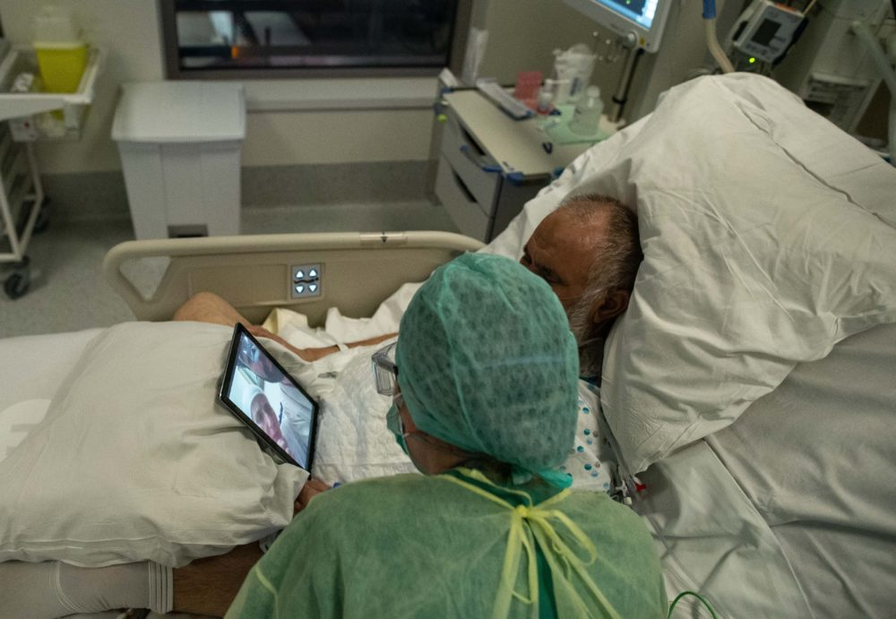 A nurse talks to the family of a patient using a tablet inside a negative pressure room  on April 10, 2020, during her night shift in the intensive care unit exclusively for COVID-19 patients in Brussels. (Aris Oikonomou/AFP/Getty Images)