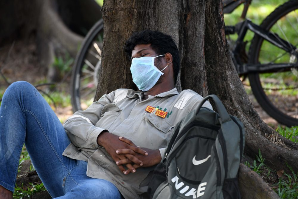 """A man wearing a face mask and a tag that reads """"Safety starts with me"""" takes a nap in Singapore on April 15, 2020. (Roslan Rahman/AFP/Getty Images)"""