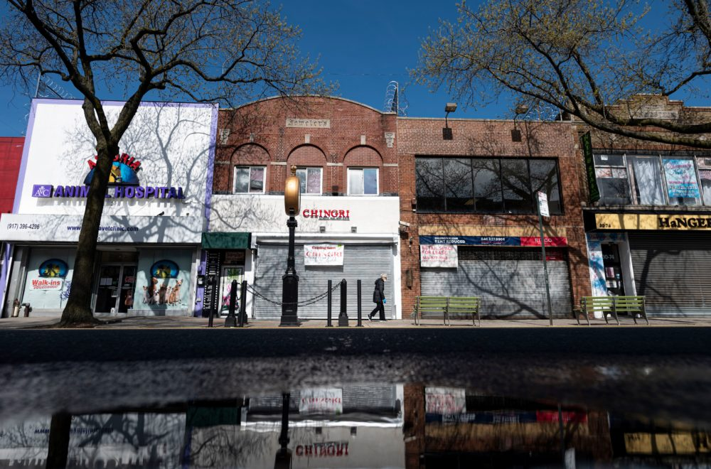 A woman wearing a mask walks past closed store fronts in the Astoria neighborhood of Queens, on April 15, 2020 in New York City. (JOHANNES EISELE/AFP via Getty Images)