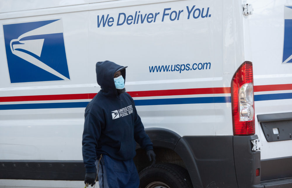 A mailman wearing a mask and gloves to protect himself and others from COVID-19 loads a postal truck with packages at a United States Postal Service (USPS) post office location in Washington, D.C., April 16, 2020. (Saul Loeb/AFP via Getty Images)
