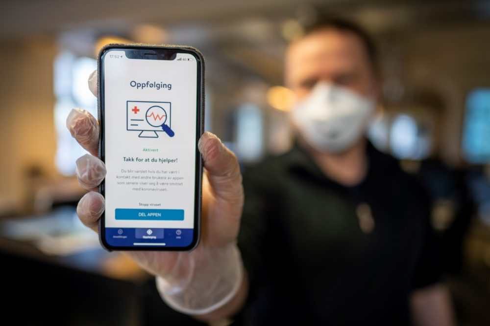 A man holds a smartphone showing a tracking and tracing app launched by the National Institute of Public Health to try to halt a return of the new coronavirus, on April 17, 2020 in Oslo. (Heiko Junge /NTB Scanpix/AFP via Getty Images)