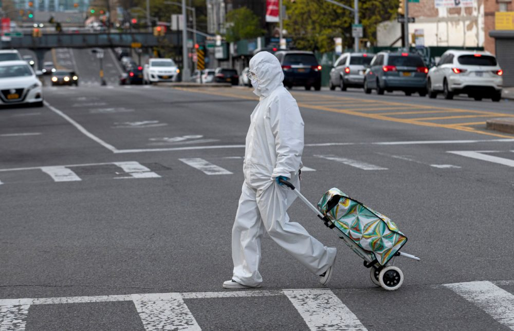 A woman wearing a hazmat suit and goggles pulls her grocery cart in the streets in Queens, a borough of New York City, amid the coronavirus pandemic on  April 20, 2020 in New York City.(Johannes Eisele/AFP via Getty Images)
