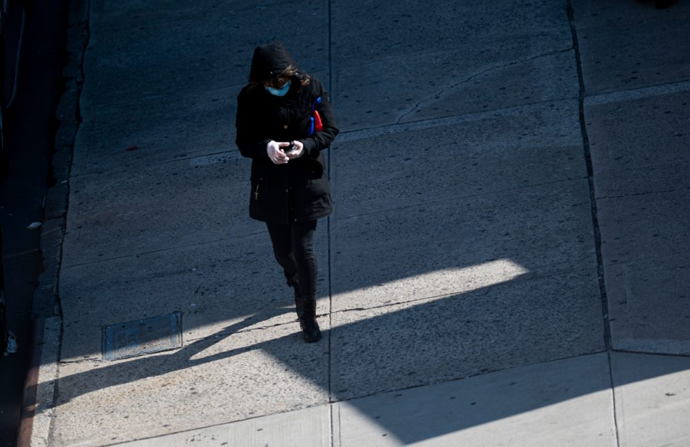 A woman wearing a mask and gloves tries to use her cellphone on April 22, 2020 in the Queens borough of New York City. - The US -- with nearly 45,000 deaths and more than 800,000 coronavirus infections -- is the hardest-hit country, and healthcare infrastructure in major hotspots such as New York City has struggled to cope. (Johannes Eisele/AFP via Getty Images)