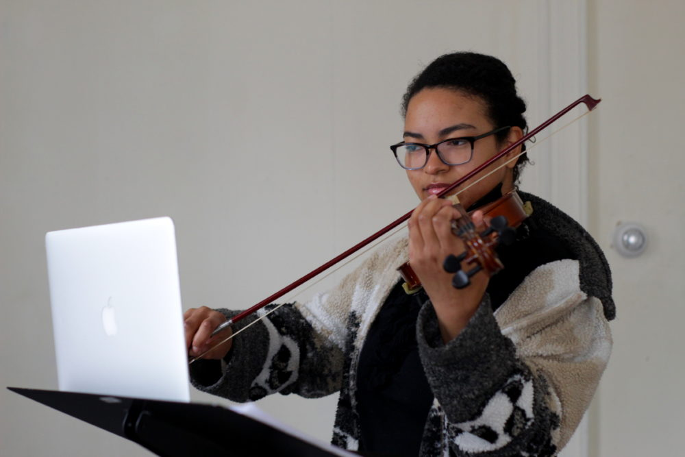 Brittany Kinch, 24, of Jamaica Plain takes a violin lesson virtually during quarantine. (Courtesy Sajada Domino)