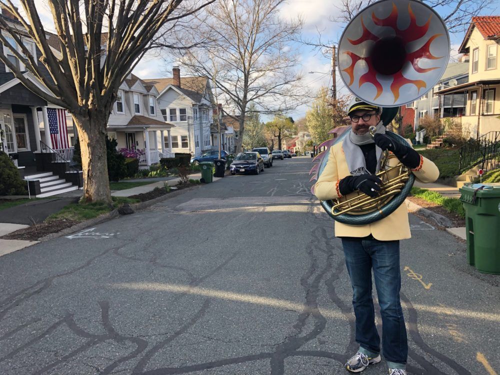 Zack Hickman plays his sousaphone on the streets of Watertown. (Bruce Gellerman/WBUR)