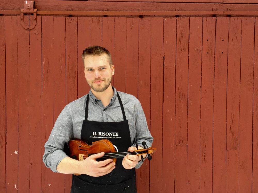 Luthier Jacob Brillhart holding one of the violins he made. (Courtesy Aneleisa Gladding-Hinton)