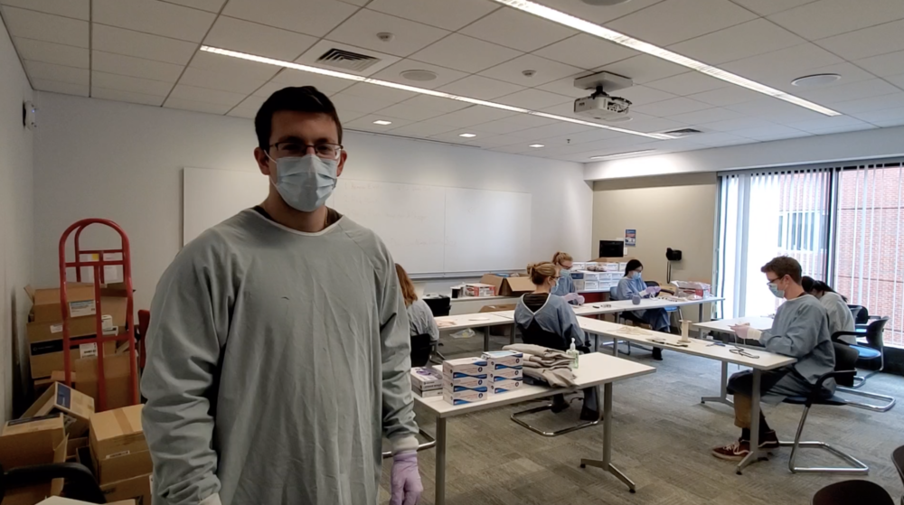James Aronson oversees a makeshift assembly line for repairing expired N95 face masks at the Tufts Dental School (Screenshot of Tufts video)