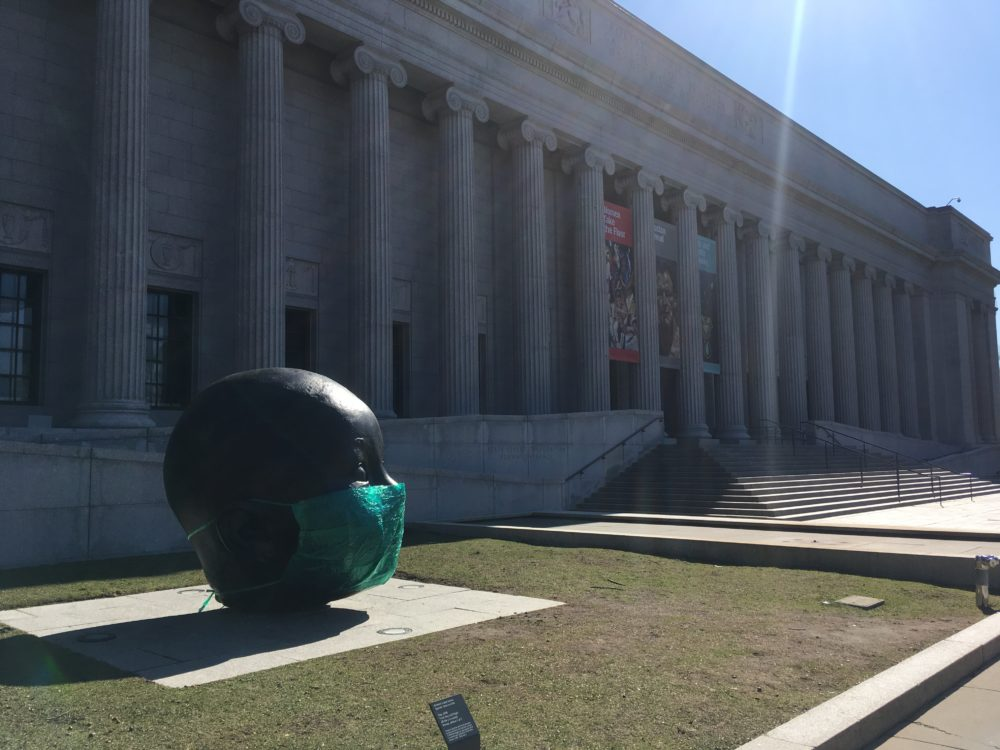 "In a guerilla art installation, Boston artist Peter Agoos placed a supersized surgical mask he created over Antonio López García's sculpture ""Day,"" which stands outside the Museum of Fine Arts. (Courtesy Peter Agoos)"