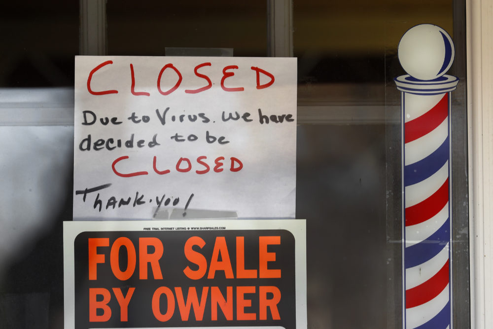 """""""For Sale By Owner"""" and """"Closed Due to Virus"""" signs are displayed in the window of a business in Grosse Pointe Woods, Mich., on April 2. (Paul Sancya/AP)"""