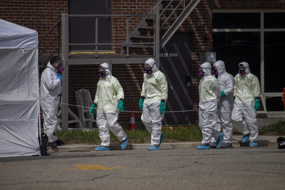 A cleaning crew suited up with protective gear enters the Soldiers Home — a state-run long-term residence and health facility in Holyoke where 11 veterans have died following a coronavirus outbreak — on March 31. (Jesse Costa/WBUR)