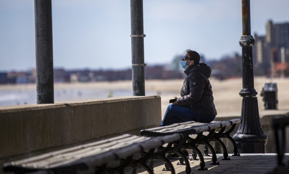 A woman sits alone in an empty pavilion at Revere Beach. (Jesse Costa/WBUR)
