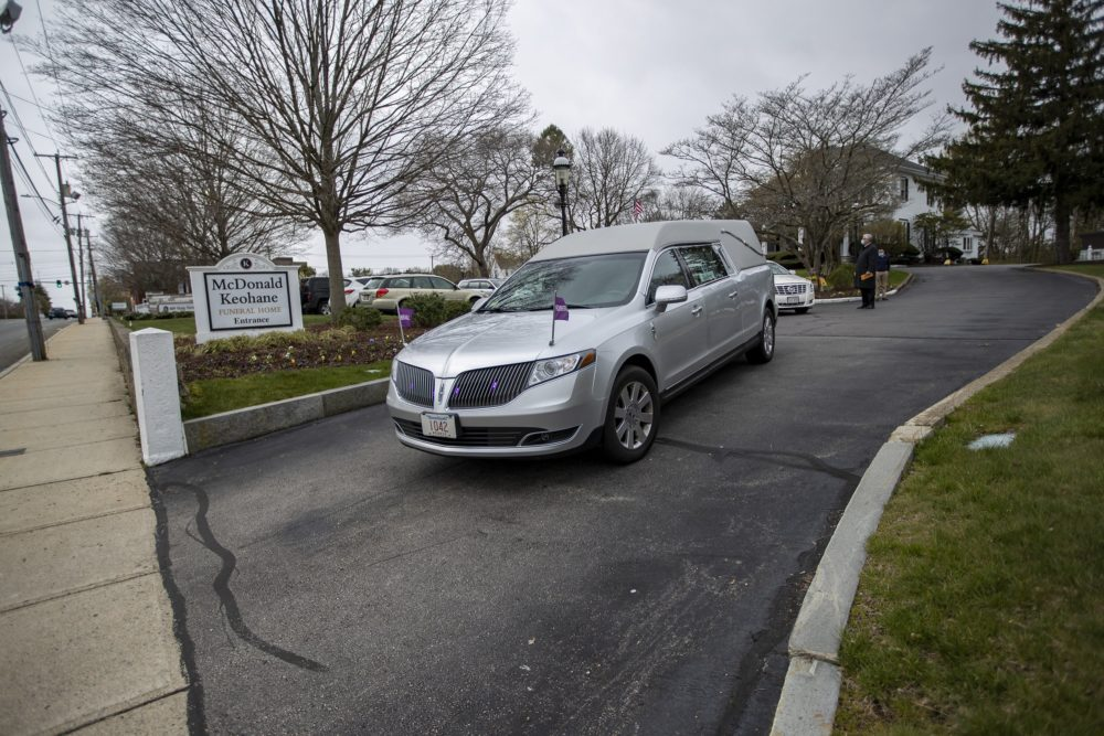 A hearse leaves the McDonald Keohane Funeral Home as it leads a procession to a nearby cemetery in Weymouth. (Jesse Costa/WBUR)