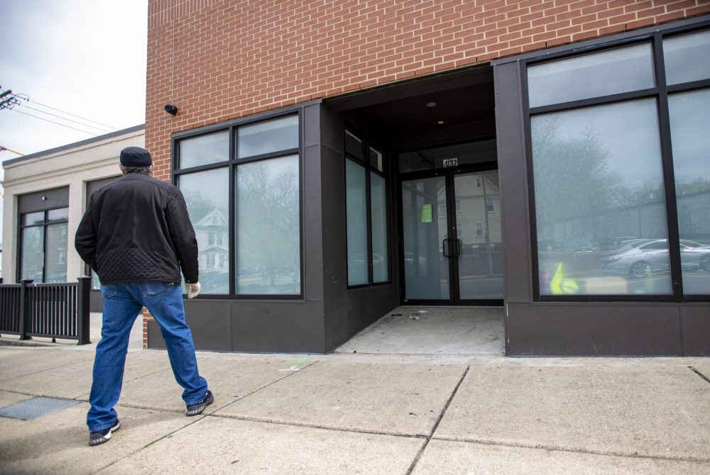 A man stops to look at shuttered Pure Oasis, a recreational cannabis shop which just opened in early March in Dorchester. (Jesse Costa/WBUR)