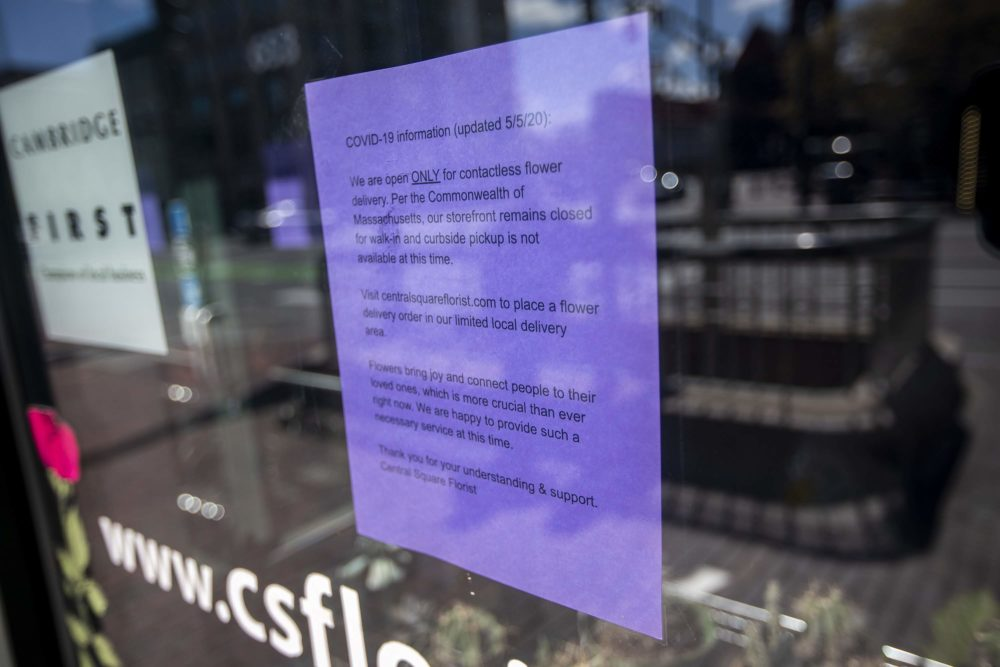 A sign in the window of Central Square Florist in Cambridge, informs customers of their new operating procedures, now that the COVID-19 restrictions for some non-essential businesses in Massachusetts have been lifted, including florists. (Jesse Costa/WBUR)