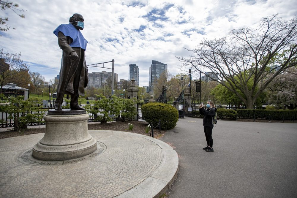 A woman takes a photo of a masked statue of Edward Everett in the Boston Public Garden. (Jesse Costa/WBUR)