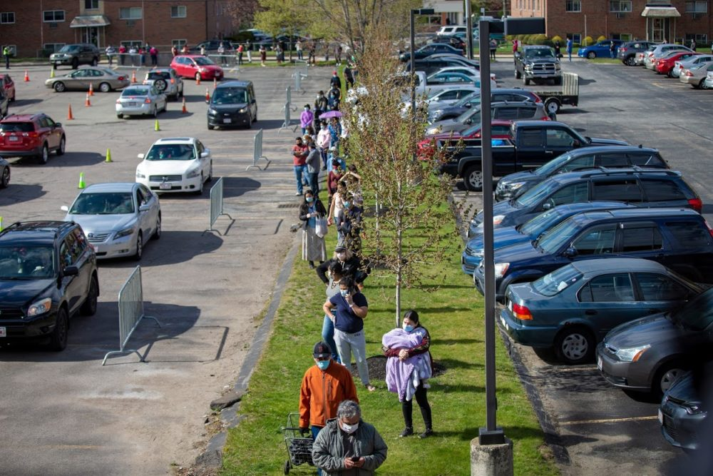 The line for food extends out of the parking lot and down Pond Street at a food pantry at St. Mary Parish in Waltham. People lined up on foot and in their vehicles at St. Mary Parish in Waltham where nearly 3,000 bags of groceries were passed out to families in need. (Jesse Costa/WBUR)