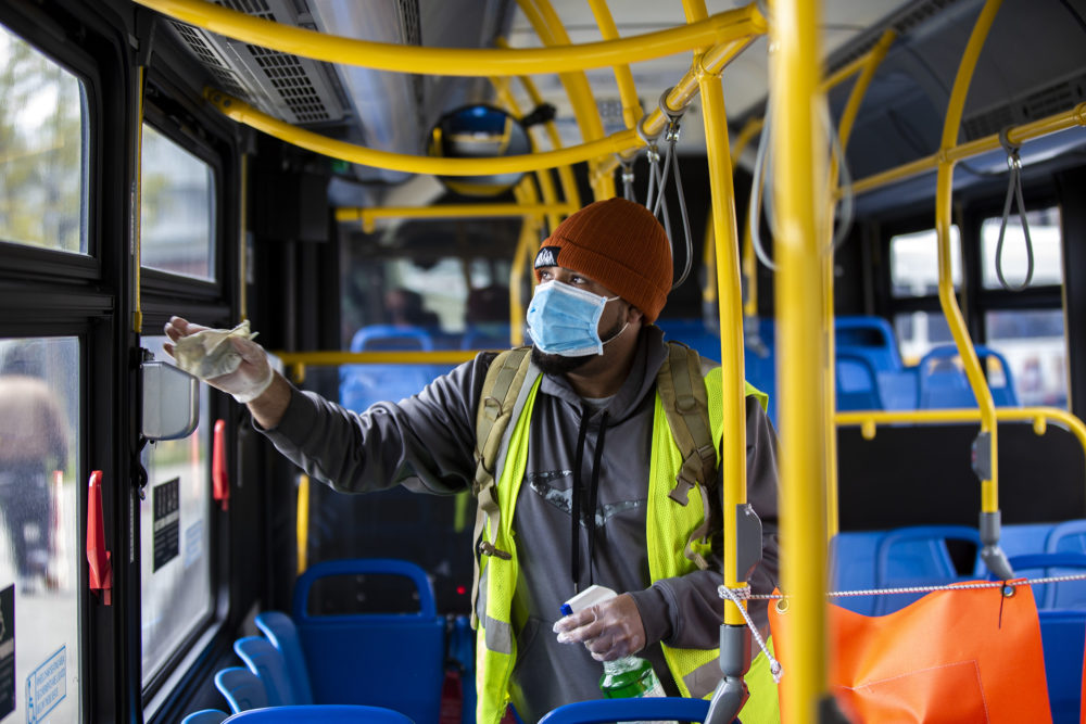 Marino Diaz Cruz wipes down the surfaces inside an MBTA bus with disinfectant after it pulled into Ashmont Station From Jackson Square. (Jesse Costa/WBUR)