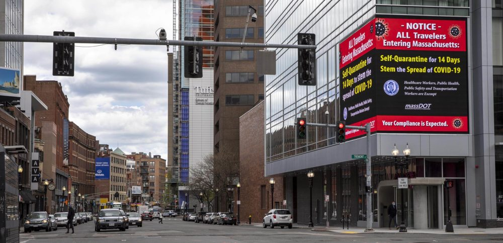 A sign on Tremont Street urges travelers to Boston to quarantine for 14 days. (Robin Lubbock/WBUR)