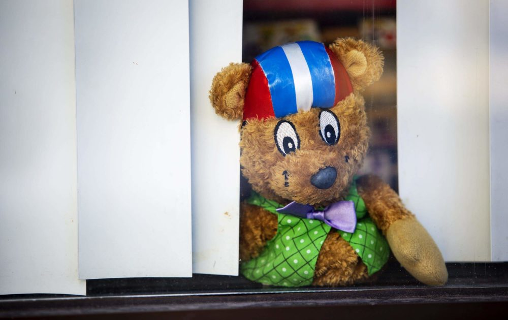 A stuffed toy looks out through the shades of a window onto the street at Play Academy in Medford, perhaps wondering when his friends will return. (Robin Lubbock/WBUR)