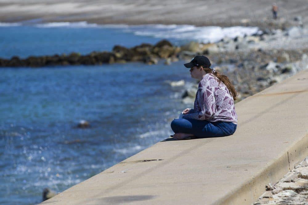 A woman sits alone on the seawall of Brant Rock Beach. (Jesse Costa/WBUR)
